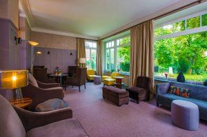 Wintergarten Lounge der Eventlocation Villa Leonhart mit gemütlichen Möbeln und Blick auf den Rhein